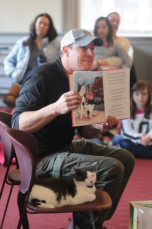 Newburyport; Toto the Tornado Kitten sits quietly as her owner Jonathan Hall reads a bout about her at the Newburyport Library Saturday. Toto was rescued from a tree after a tornado hit western Mass in 2011 and was adopted by EMT Hall, who wrote a book about the cat's rescue and recovery. Jim Vaiknoras/staff photo