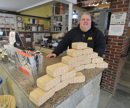 Amesbury: Kevin Lordan , manager of Martignetti Enterprises, stand next to a display of Hot Bricks, a compressed saw dust product for use in fire places and wood stoves. Martignetti's like most businesses have been trouble keeping pellets for pellet stoves in stock.Jim Vaiknoras/staff photo