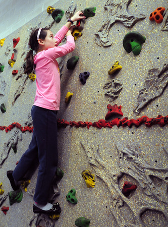 """Amesbury: Adelaide Saltsman, 9, climbs the rock wall in phys ed class at Amesbury Elementary School on Tuesday. Teacher Margaret Welch let the fourth-graders do some unstructured """"choice time"""" letting them choose an activity of their choice to unwind after a day of MCAS tests. Bryan Eaton/Staff Photo"""