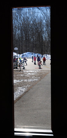 Newbury: Newbury Elementary School children play during recess after exiting the lunchroom through this door. The weather looks good for outdoor recess through the rest of the week as temperatures finally gets springlike. Bryan Eaton/Staff Photo
