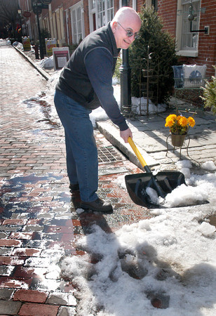 Newburyport: Sunlight reflects off melting snow on Inn Street in Newburyport as Brass Lyon owner Ed Gronbeck took advantage of the 50 plus degree temperature to break up snow yesterday afternoon in front of his shop. Winter returns today as rain starts to come in late in the day and turns to snow overnight with a couple of inches forecast. Bryan Eaton/Staff Photo