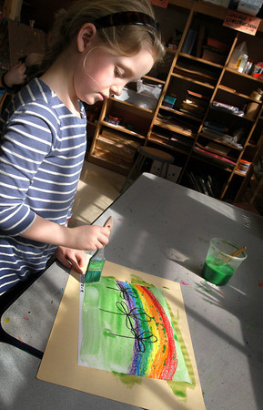 """Newburyport: With Judy Garland singing """"Somewhere Over the Rainbow"""" in the background, Georgia Nichols, 6, paints a rainbow in art class at the Brown School. Pam Jamison was teaching the students about light and the colors formed when it's refracted through a prism, and to be timely for St. Patrick's Day had the children paint shamrocks on the rainbows. Bryan Eaton/Staff Photo"""