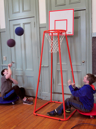Newburyport: Jason Howes, 13, left, and Jack Bryk, 12, practice shooting baskets, though while cruising around on scooters. They were at the Kelley School Youth Center on Wednesday afternoon. Bryan Eaton/Staff Photo