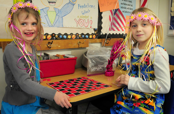 Newburyport: Emma MacIsaac, 6, left, and Natalie DeGraves, 7, play a game of checkers during indoor recess Monday in Stacey Boucher's class at the Bresnahan School. The youngsters were dressed in Hawaiian clothing in a jab to the long winter, the children having some fun as they reached a milestone for positive behavior in class. Bryan Eaton/Staff Photo