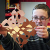 Newburyport: Shane Smith, 13, shows off his paper snowflake to fellow students at the Kelley School Youth Center. They were cutting out different paper patterns and designs. Bryan Eaton/Staff Photo