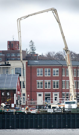 Newburyport: A concrete pump towers over buildings on the Newburyport waterfront in a view from Ring's Island in Salisbury on Thursday. It was used in the reinforcement of the boardwalk. Bryan Eaton/Staff Photo