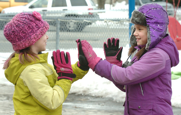 """Amesbury: Gianna Surprenant, left, and Sarah Chace, 9, play a game of """"Avocado"""" which appeared to be a lot like the game """"Pattycake"""" while getting some fresh air at Amesbury Elementary School. The two were in the Amesbury Recreation Department's Afterschool Program which hasn't been able to use the playground as it is still under a foot of very icy snow. Bryan Eaton/Staff Photo"""