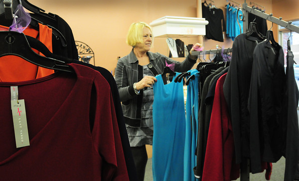 Amesbury: Deb Pagley of Parke Place Boutique puts spring dresses onto hanger in her downtown Amesbury shop. Bryan Eaton/Staff Photo