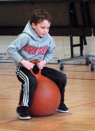 """Newburyport: Grady Smith, 5, tries to get the hang of a bouncy ball in Chris Gogolos' physical education class at the Brown School on Wednesday. They were doing their own version of Read Across America after reading the Seuss book """"Hop On Pop."""" Bryan Eaton/Staff Photo"""