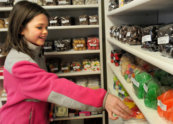 Amesbury: Elizabeth Cronin, 9, who has been coming to Carriagetown Chocolates since she was a tot, chooses some candy there yesterday. Bryan Eaton/Staff Photo