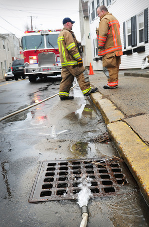 Newburyport: Firefighters pump out a flooded basement at Merrimac and Merrill Streets yesterday morning. They only had a couple calls but expected more as the groundwater starts to rise and more rain was forecast for last night. Bryan Eaton/Staff Photo