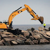 Newburyport: An excavator moves rocks at the eastern end of the south jetty of the Merrimack River yesterday afternoon. Work is sceduled to conclude on March 31 on the repair project that should help ease erosion in the long term on Plum Island.  Bryan Eaton/Staff Photo