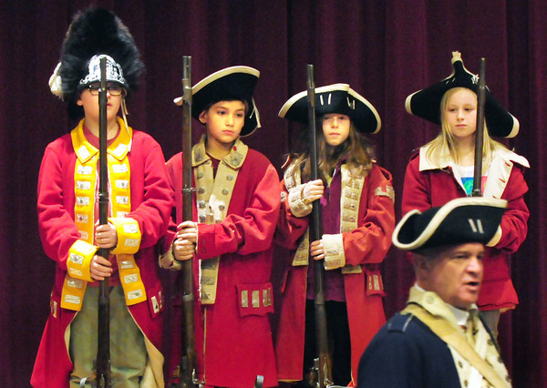 "Amesbury: Amesbury Middle School sitxh-graders, from left, Max Exter, Jeremy Lopez, Nina Sesto and Faith Purvis, dressed as British Redcoats, stand at attention as presenter David Cormier is dressed as an officer in General Washington's regiment speaks. Cormier's ""Hands on History"" presentation showed artifacts from the Revolutionary War and described life during that period. Bryan Eaton/Staff Photo"