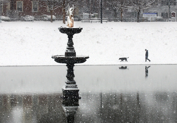 BRYAN EATON/Staff Photo. A lay and her pooch walk along the fallen snow at the unfrozen Frog Pond at the Bartlet Mall in Newburyport on Monday morning. Skies cleared later and with the temperature rising to 45 degrees the snow started to melt quickly.