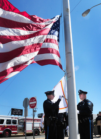 Salisbury: Salisbury police officers Christopher Thurlow, left, and Brian Smith raise National Peace Officers Memorial Day flag under the American flag at a ceremony at Salisbury Beach. Bryan Eaton/Staff Photo
