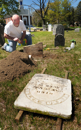Salisbury: Paul Turner applies a special epoxy to broken gravestone of Simeon Eaton at the Salisbury Colonial Burying Ground. The new chair of the Salisbury Historical Commission has been repairing several other stones in disrepair in the town-owned cemetery founded in 1639. Bryan Eaton/Staff Photo