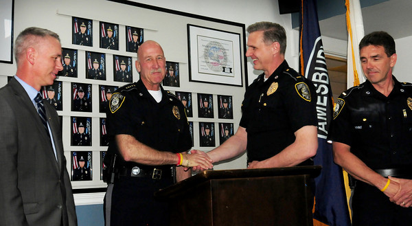 Amesbury: Retiring Amesbury police chief Mark Gagon, second from left, congratulates his successor, Lt. Kevin Ouellet, as Mayor Thatcher Kezer, left, and Lt. Jeffrey Worthen look on. Bryan Eaton/Staff Photo