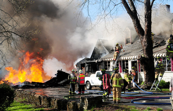 West Newbury: Firefighters from West Newbury and surrounding communities attack the fire at the house which was attached to the barn that burned, left. Bryan Eaton/Staff Photo