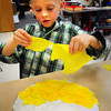 Newbury: Mason Colby, 6, rips pieces of thin paper at Newbury Elementary School. The youngster was making a sunflower as his class was learning about flowers. Bryan Eaton/Staff Photo