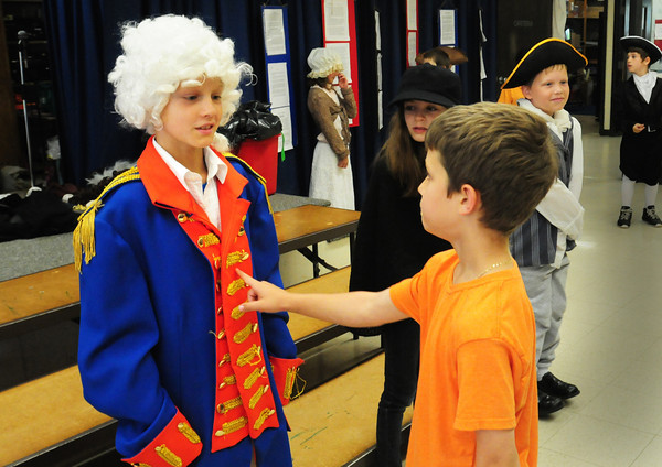 """Amesbury: Tyler Bartniski, 7, right, pushes an imaginary button to bring to life """"King George III"""" aka Will Legg, 9, at a wax museum at Amesbury Elementary School. The museum was one of several projects on display throughout the school for their """"Celebration of Learning."""" Bryan Eaton/Staff Photo"""