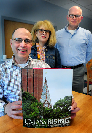 Amesbury: Peter Blaiwas, creative director, left, and Brian D. Hotchkiss, executive director, right, both of Vern Associates show the book they produced on the University of Massachussets pictured with alumni Carolyn Russell, class of 1980. Bryan Eaton/Staff Photo
