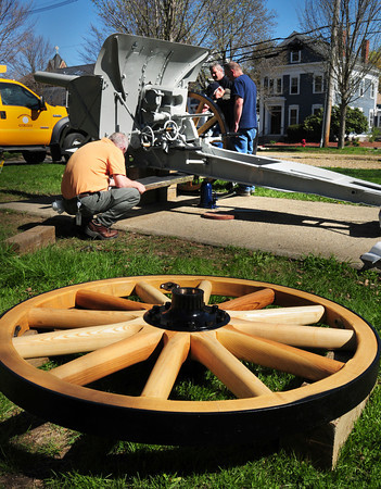 """Newburyport: City workers attach one of the two wheels to the World War I era German howitzer at the Bartlet Mall yesterday morning after they were taken off in October to be refurbished. The 105mm gun was dedicated on Veteran's Day in 1931 for """"those whom made the supreme sacrifice in the war to end all wars."""" Repairs had been done previously in 1990 as well. Bryan Eaton/Staff Photo"""