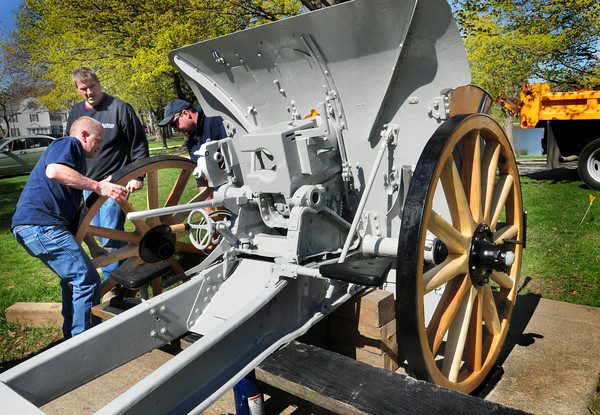 """City workers attach one of the two wheels to the World War I era German howitzer at the Bartlet Mall yesterday morning after they were taken off in October to be refurbished. The 105mm gun was dedicated on Veteran's Day in 1931 for """"those whom made the supreme sacrifice in the war to end all wars."""" Repairs had been done previously in 1990 as well. Bryan Eaton/Staff Photo"""