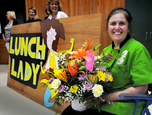 """Merrimac: School """"lunch lady"""" Linda Vienneau at the Sweetsir School was given flowers by her daughter, Julie, at a school assembly there on Thursday. She was honored by the School Nutrition Associaton of Massachusetts and was a surprised by the award at the assembly. Bryan Eaton/Staff Photo"""