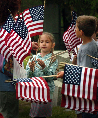 Amesbury: Skyla McBride, 8, gets her allotment of flags to place on the graves of veterans at the Mt. Prospect Cemetery in Amesbury. The third grade students have been replacing the worn out flags at the cemeteries and memorials for many years learning about the sacrifices of those who fought in America's wars. Bryan Eaton/Staff Photo