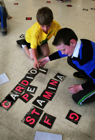 Newburyport: Caelan Twichell, left, and Liam Casco, both 8, spell words as they hopped around the Bresnahan School cafeteria in that class looking for letters spread about. The second-graders in Jesse Craddock's class used the excercise to review words they've learned related to physical education class. Bryan Eaton/Staff Photo