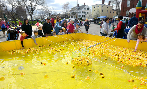JIM VAIKNORAS/Staff photo Kids , and adults play with rubber ducks in a large pool at the Newburyport Youth Services Duck Derby at the Mall in Newburyport Sunday.