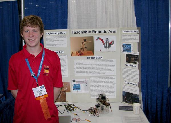 Newburyport's Mark Landergan with his science project , a teachable robotic arm.