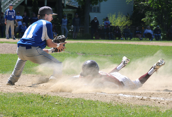 JIM VAIKNORAS/Staff photo Georgetown first baseman Ben Bottlinger waits for the throw as Newburyport's Caleb Stott slides safely back to first during their championship game in the annual Bert Spofford Baseball Tournament at Georgetown Sunday. The Clippers won the game 8-5.