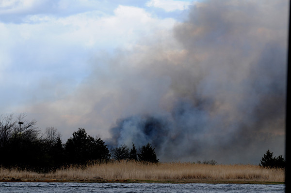 JIM VAIKNORAS/Staff photo  Smoke rises from a fire in the marsh off Ferry Road in Salisbury as seen from across the Merrimack River in Newburyport.
