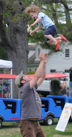 JIM VAIKNORAS/Staff photo Rutherford Rogers, 2, gets tossed in the air by his dad Kieth during the Strut for Stays annual walk and celebration on teh Upper Green in Newbury Sunday morning.