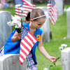 JIM VAIKNORAS/Staff photo SMadeleine Jackman , 5,  places daisies on on head stones at Veterans cemetary in Newburyport following  the annual Newburyport Memorial Day service.