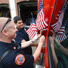 JIM VAIKNORAS/Staff photo Ianin McGregor and David Carpentier of the Amesbury Fire Dept attach flags to one of their ambulances before the start of Amesbury annual Memorial Day Parade.