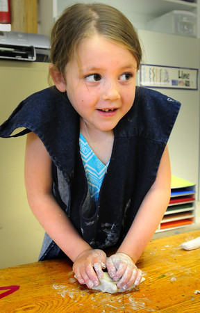 BRYAN EATON/ Staff Photo. Julianna Guimaraes, 5, uses her strength to press down and mold clay in Sara Connor's art class. The Amesbury Elementary School kindergartners were making butterflies.