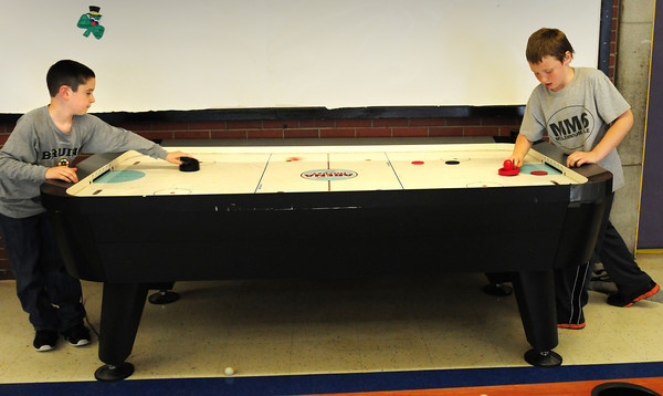 "BRYAN EATON/ Staff Photo. Damien Fry, 9, left, and Jacob Coady, 11, play a game of what they call ""extreme hockey"" at the Boys and Girls Club. Instead of using one puck at a time, they use four to up the skill level."