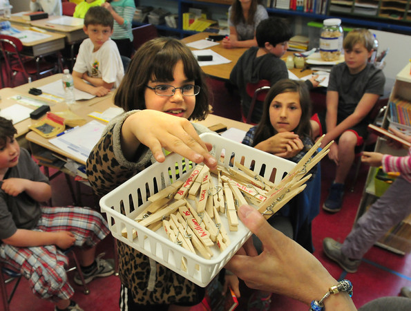 BRYAN EATON/ Staff Photo. Melody Coker, 10, grabs a clothespin from Amesbury Elementary School teacher Sheila Harney which has students in the classroom's names on them. They were drawing to choose from different books that were donated to each fourth-grader in the Amesbury school system. Nick Emerson, who won this year's Top Chef competition and whose mother, Florence Emerson teaches at the Cashman School and sister Sally Heckerman at the elementary school, had arranged for the gifts through an associaton with Scholastic Book Company.