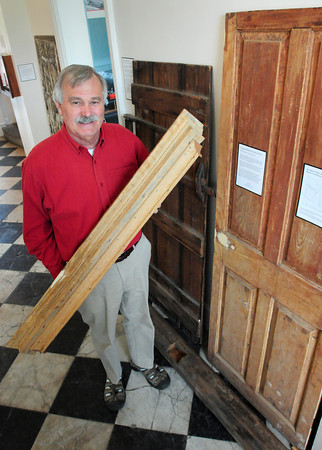 BRYAN EATON/ Staff Photo. Tom Kolterjahn holds a Federalist window entablature, which topped windows, made of old growth pine from around 1810 which was found in a dumpster on High Street in Newburyport. Behind him is a doweled hinge batten door from around 1710 and to the right a Georgian raised four panel door from about 1760. These items are on display at the Custom House Maritime Museum with others, many of which were discarded and rescued for their historic value.