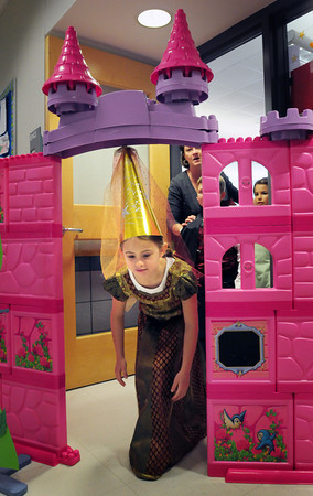 BRYAN EATON/ Staff Photo. Molly Orroth, 7, has to duck down to get under the castle gate at Salisbury Elementary School. FIrst-graders were holding a Fairy Tale Day and went to different classrooms for various activities.