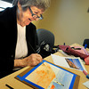 """BRYAN EATON/ Staff Photo. Ann Marie Garnett of Newburyport paints from a photo of a lighthouse in """"Art With Cara"""" at the Amesbury Senior Center. Cara Smoley teaches painting every Monday where those with no experience are welcome."""