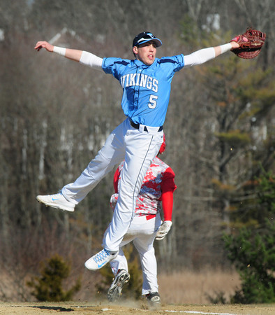 BRYAN EATON/Staff Photo. Masconomet's Elias Varinos gets past Triton's airborne first baseman Adam Chatterton.