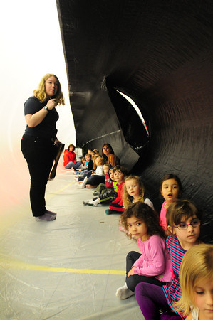 BRYAN EATON/ Staff Photo. Children at Mrs. Murray's Nursery School in Newburyport look down the inside of a blowup finback whale which is the second largest animal in the world. Abby Gronberg, pictured, from The Blue Ocean Society for Marine Conservation was teaching the children about the oceans.