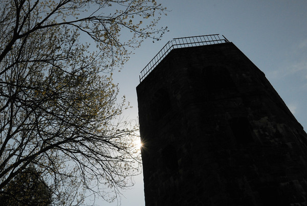 BRYAN EATON/ Staff Photo. Leaves are spurting out from these trees framing the tower at Atkinson Common in Newburyport. The tower was built in 1935 and replaced an earlier wooden structure.