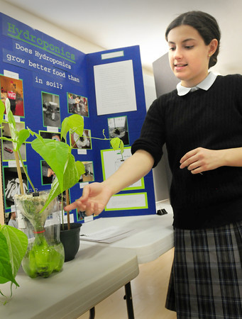 "BRYAN EATON/ Staff Photo. Lily Walsh, 13, explains her project ""Does Hydroponics Grow Better Food?"" which she found out does. She was in the Immaculate Conception School's Science Fair on Tuesday night."