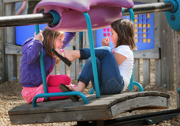 BRYAN EATON/ Staff Photo. Evie Pifalo, left, and Annah Belisle, both 7, spend time chatting on a tram in the playground at Amesbury Elementary School while other youngsters were playing on other playthings. They were at the Amesbury Recreational Department's Afterschool Program.
