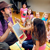 BRYAN EATON/ Staff Photo. A presenter from Mystic Drumz goofs as children take turns rubbing a nickel along a washboard at Salisbury Elementary School on Tuesday. The six week program through the afterschool program Kids Club introduces 160 instruments from around the world to the youngsters.