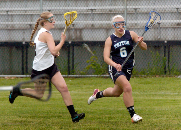 BRYAN EATON/ Staff Photo. Triton's  Lily Dow heads down the field with Newburyport's Olivia Kearney in pursuit.